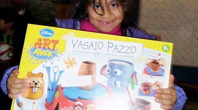 Una bambina riceve uno dei giocattoli donati dai lettori di Bergamonews