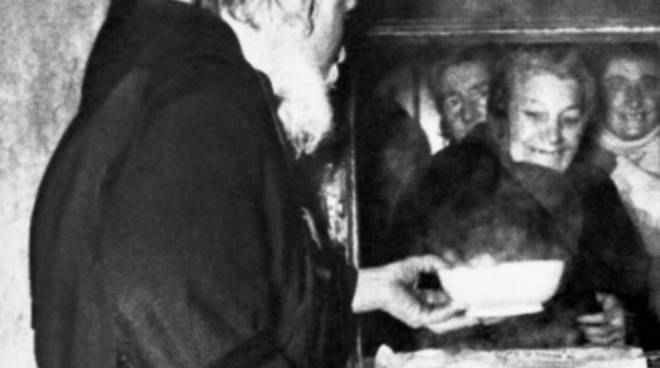 Una foto di archivio che mostra Fra Cecilio mentre distribuisce ai poveri il piatto di minestra